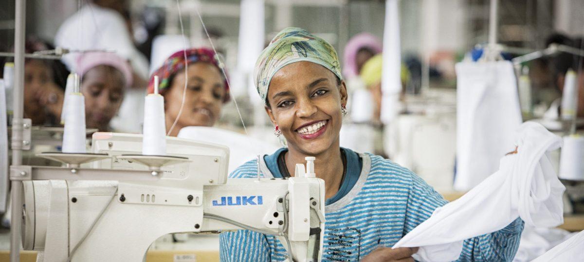 Ethiopische vrouw zit achter een naaimachine en kijkt lachend in de camera. Zij heeft een blauw gestreept shirt aan en heeft een stuk witte stof in haar handen.